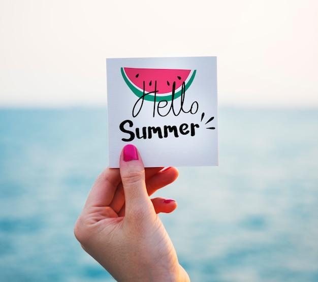 해변에서 여름 그래픽이 있는 메모를 들고 있는 여자