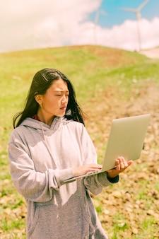 노트북을 들고 언덕의 배경에 서있는 여자