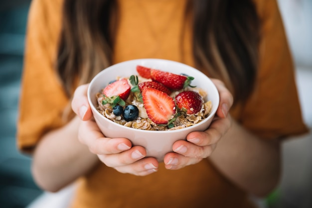 Woman holding oatmeal with berries in bowl