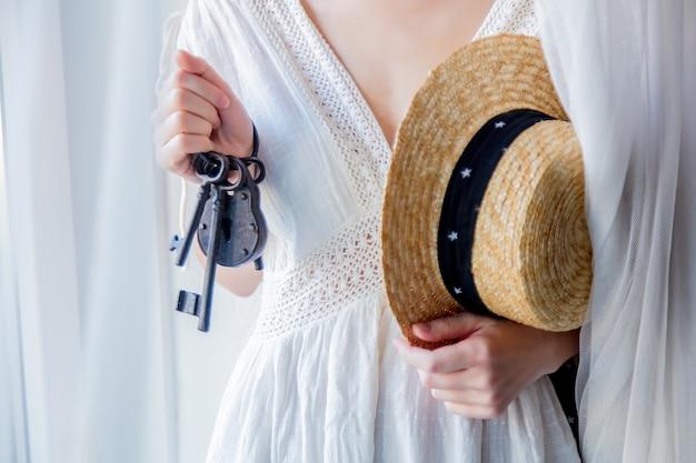 여자 손에 오래 된 키와 자물쇠를 들고 자연 채광과 함께 창 근처에 머물