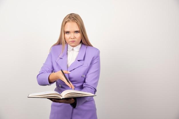 白で開いたタブレットを保持している女性。