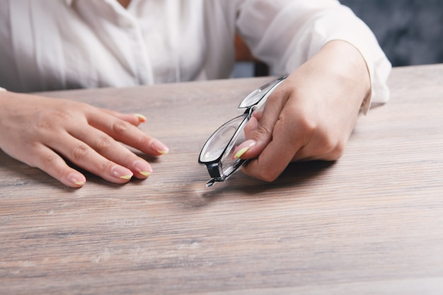 탁자 옆에 앉아 있는 동안 광학 안경을 들고 있는 여성