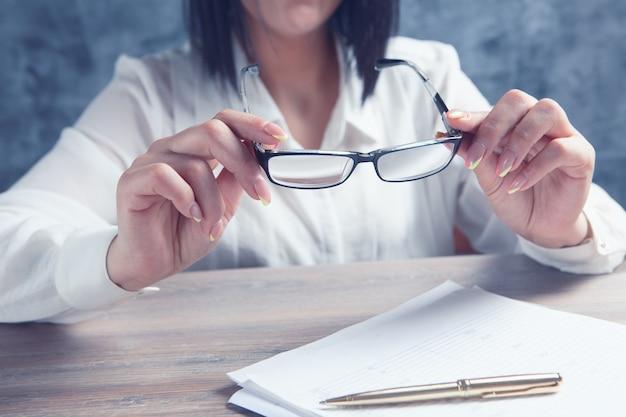 テーブルのそばに座って光学メガネを保持している女性