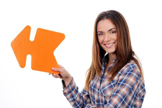 白い背景で隔離オレンジ色の矢印を保持している女性
