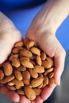 Woman holding organic almond nuts in hands