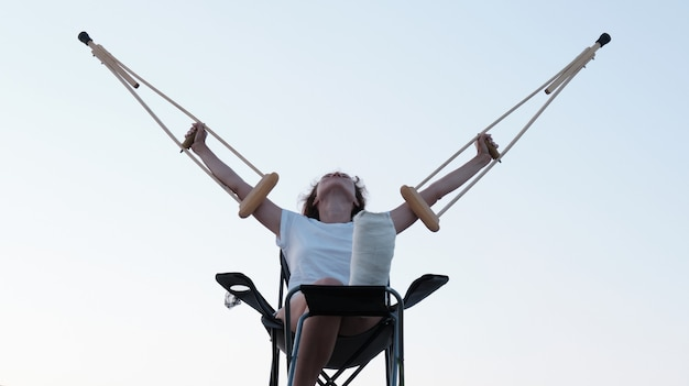 Woman holding orthopedic crutches above her head leg injury  rehabilitation after a fracture