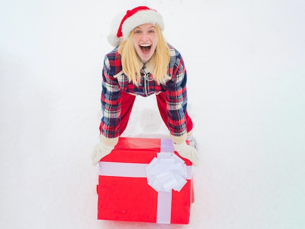 Woman holding packaged christmas gift with ribbon
