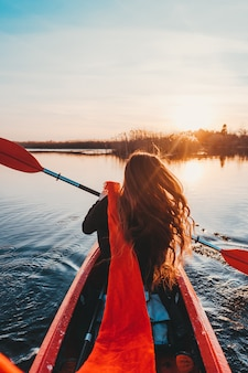 Woman holding paddle in a kayak on the river