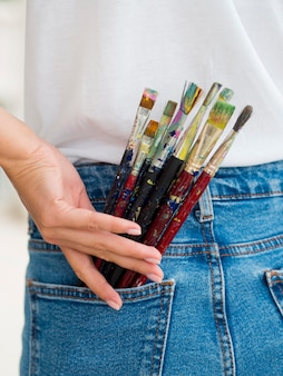 Женщина держит кисти в заднем кармане