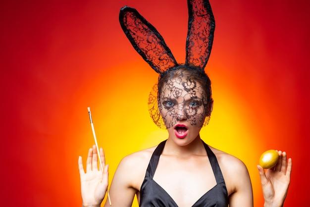 Женщина, держащая крашеные яйца. костюм заячьих ушей. молодая женщина в ушах зайчика в день пасхи.