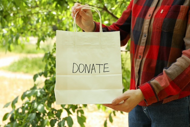 Woman holding paper bag with text donate outdoor