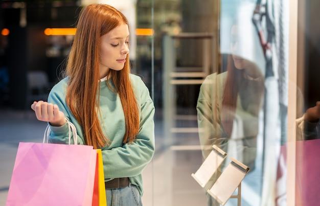 종이 가방을 들고 상점 창에서 보이는 여자