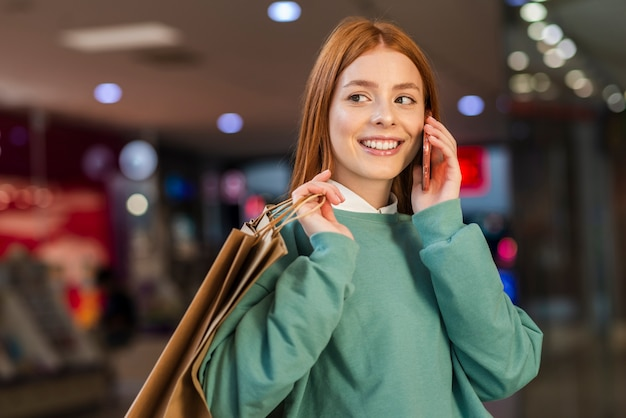 Woman holding paper bags and talking on phone