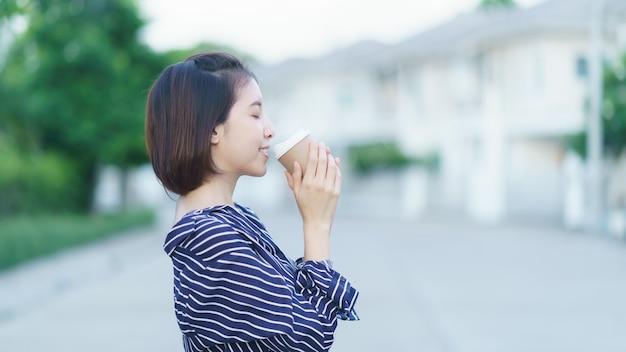奪う紙のコーヒーカップを保持している女性。