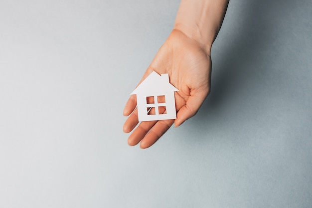 Woman holding a paper house with her hands