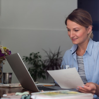 Woman holding paper and looking at laptop
