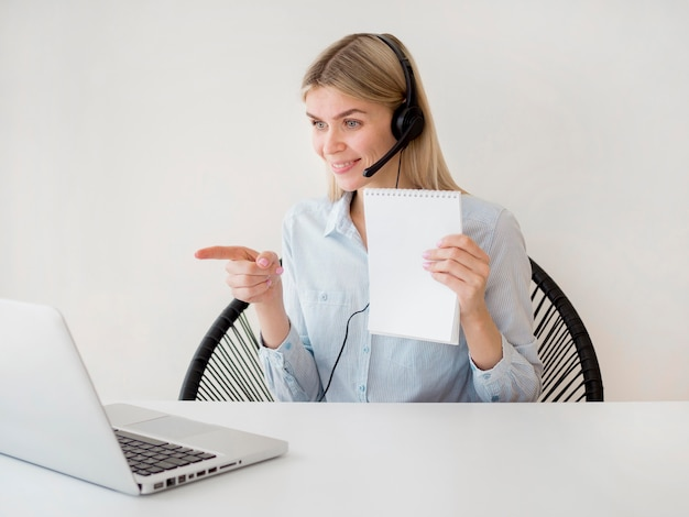 Woman holding paper and pointing to the laptop