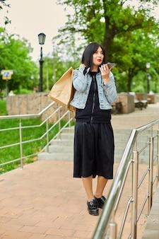 Женщина держит бумажные хозяйственные сумки и разговаривает по телефону, говоря смартфон в парке девушка после покупок