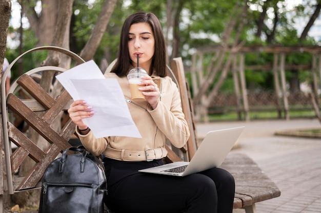 Женщина держит документы и работает на открытом воздухе