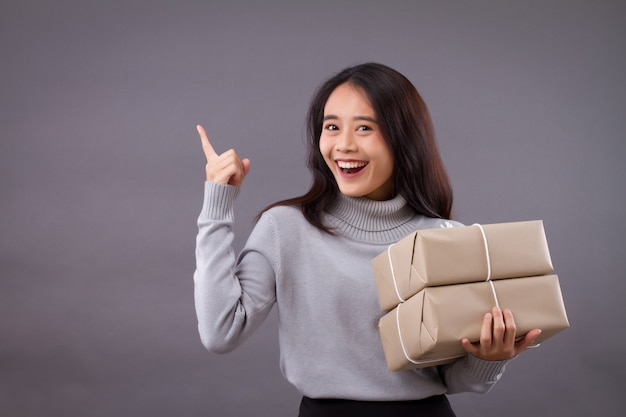 Woman holding parcel box and pointing up, isolated wall