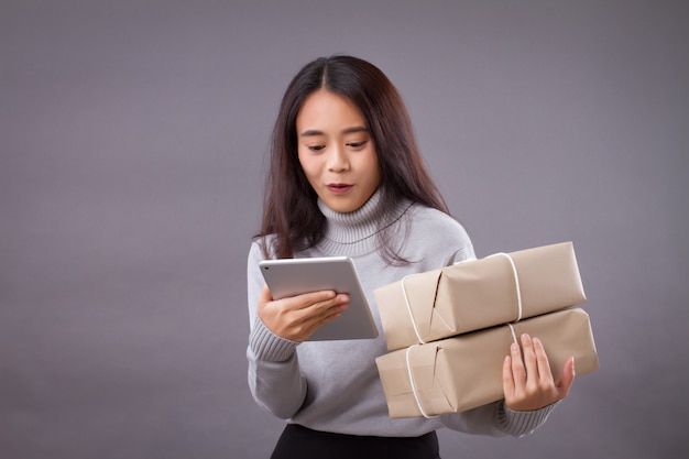 Woman holding parcel box with computer tablet, online shopping concept
