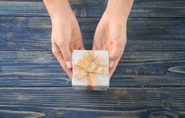 Женщина, держащая подарочную коробку посылки на деревянном фоне, вид сверху