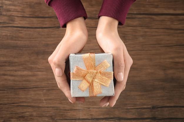 Женщина, держащая подарочную коробку посылки на деревянном столе