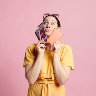 Woman holding passport and plane tickets close to her face