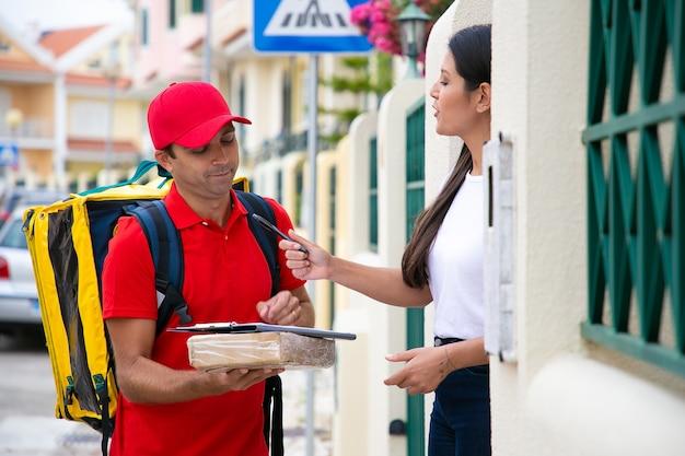 配達されたパッケージの領収書に署名するためのペンを保持している女性。荷物を持って屋外に立って顧客に注文を届ける赤い制服を着た白人のハンサムな宅配便。配送サービスとポストコンセプト