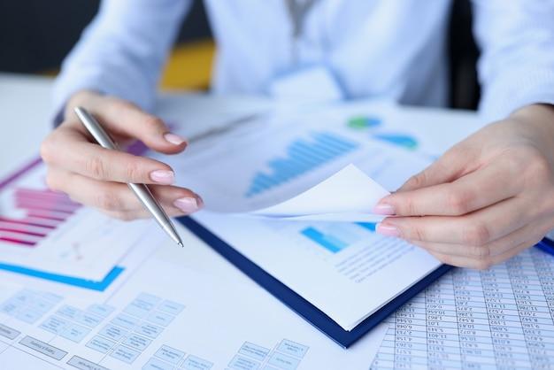 Женщина держит ручку в руках и листает документы крупным планом