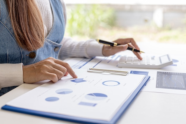 Woman holding a pen pointing to a document on her desk and pressing a calculator, she is checking the numbers on the financial documents prepared by the finance department. concept of financial audit.