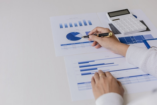 Woman holding a pen pointing to documents on a desk, she is a financial scholar, she is checking company financial documents for accuracy before presenting them to executives. financial audit concept.