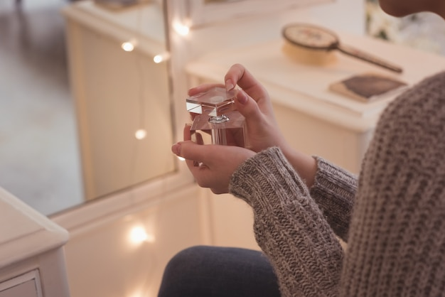 Woman holding a perfume bottle at home