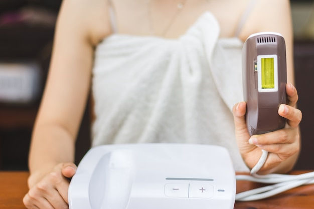 Woman holding personal ipl lase epilation prepare for skin care at home