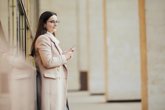 パノラマの窓に対して電話を保持している女性