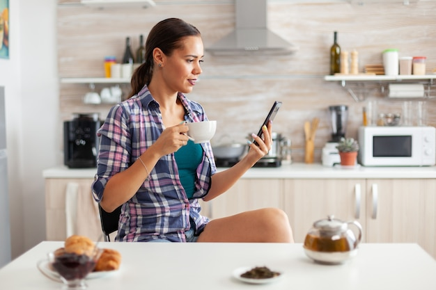 Woman holding phone and drinking hot tea with aromatic herbs in kitchen during breakfast