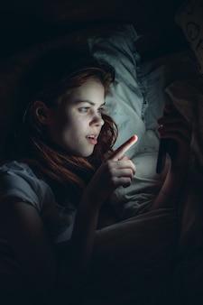 夜のライフスタイルでベッドに横たわっている彼女の手で携帯電話を保持している女性。