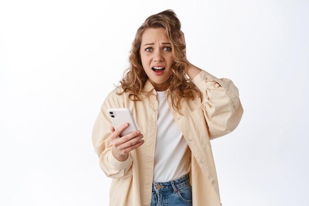 Donna che tiene il telefono e guarda in preda al panico, sentendosi ansiosa e preoccupata per qualcosa pubblicato online, in piedi con lo smartphone contro il muro bianco