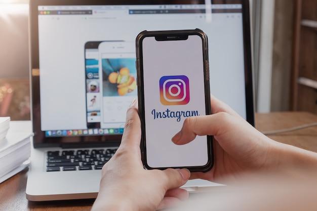 画面上のinstagramアプリケーションで携帯電話を保持している女性