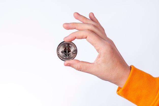 Женщина, держащая физическую монету ethereum (eth). концепции криптовалюты на белом фоне.