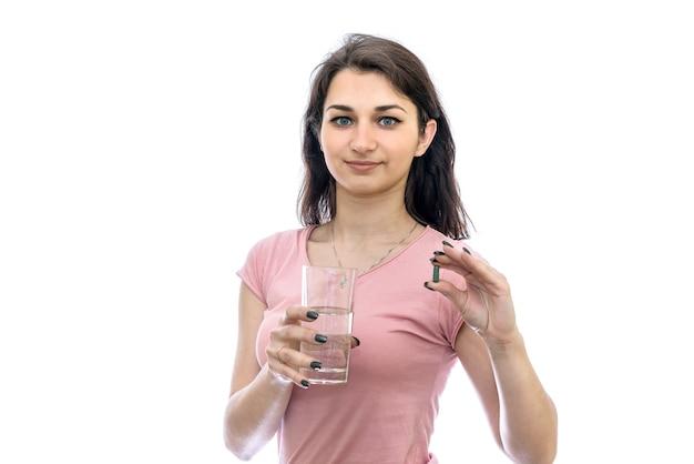 알 약과 흰 벽에 절연 물 잔을 들고 여자