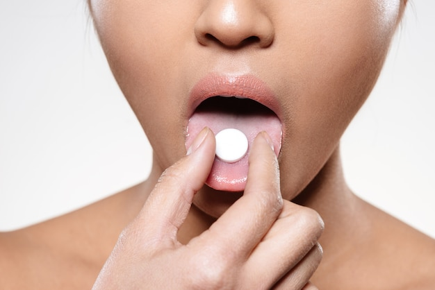 Woman holding pill in her mouth