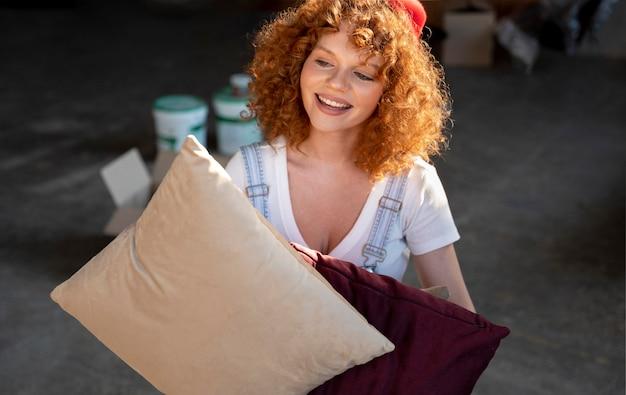Donna che tiene i cuscini per decorare la nuova casa