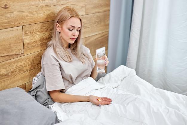 약을 복용하고 두통을 치료할 시간을 가진 여성은 집에서 고혈압 진통제 약물을 침대에 혼자 앉아 있습니다. 코로나 바이러스 covid-19 전염병 동안 집에 머물러 라.