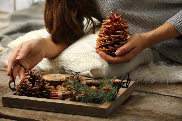 Женщина, держащая сосновую шишку и деревянную корзину с вечнозелеными, крупным планом