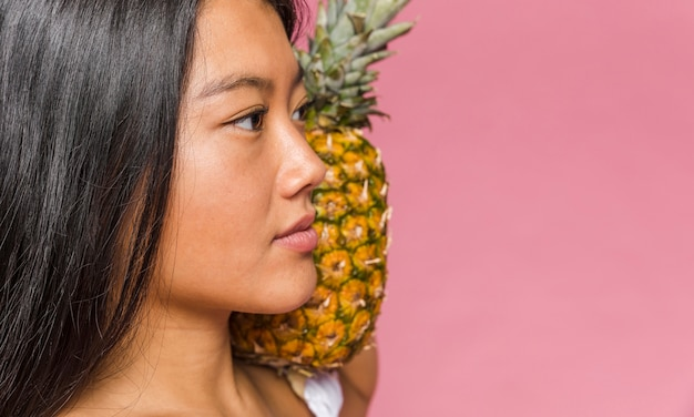 Woman holding a pineapple on her shoulder close-up