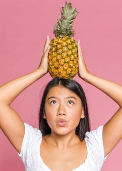 Woman holding pineapple and looking at it