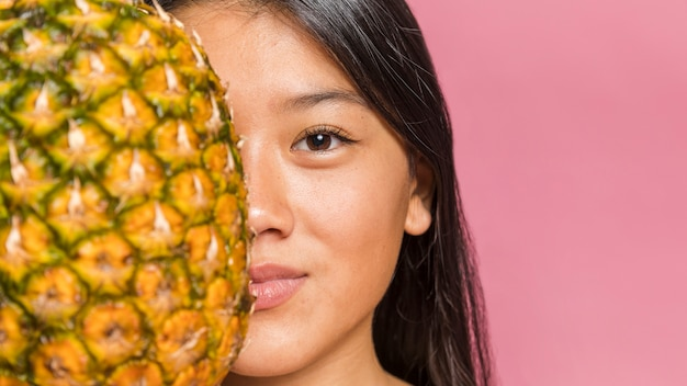 Woman holding a pineapple and smile