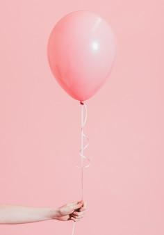 Donna in possesso di un palloncino rosa