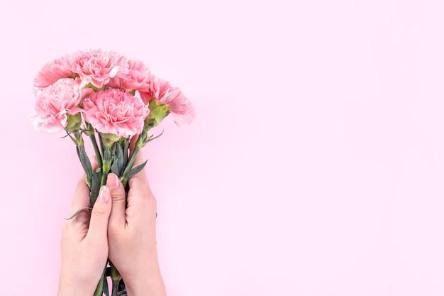 핑크 테이블 배경 위에 핑크 카네이션을 들고 여자